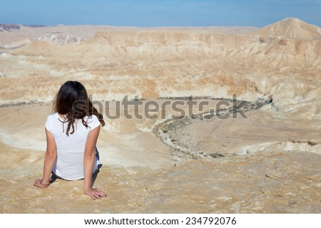 Young woman girl sitting resting on desert mountain cliff edge. Negev mountains, Israel.