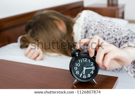 Young woman girl turns off alarm clock waking up in the morning from a call. Unrecognizable student do not want to wake up early for school or univercity. Oversleep, not getting enough sleep concept.