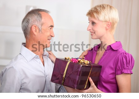 young woman giving a gift to an older man - stock photo