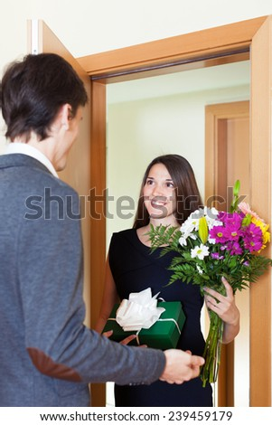 Young woman giving flowers and gift to guy near home  door
