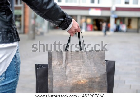 Young woman goes shopping in the City bags in her hands – selective focus selective focus and blurred background  #1453907666