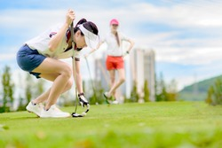 young woman golf player crouch stoop down to laying golf ball for putting to the holf on the green at golf course, golf mate buddy or opponent competitive player watching in background