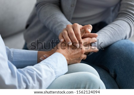 Young woman granddaughter daughter hold old female hand of mother grandma sit on sofa, two women generation help support concept, senior people parents grandparents care and comfort, close up view