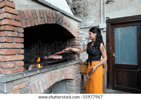 Young woman grilling some sausages on a barbecue