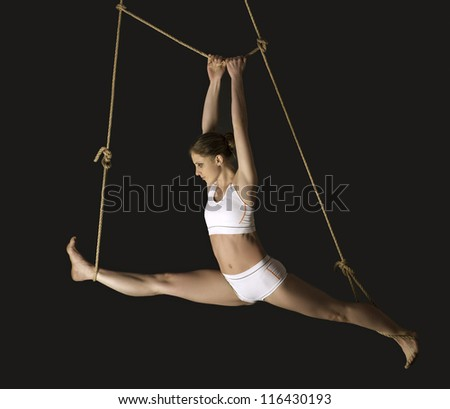 Young woman gymnast. On black background