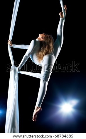 Young woman gymnast. On black background with flash effect.