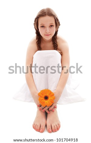young woman hand and feet with manicure and orange flower isolated on white