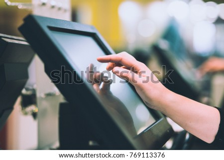 Young woman hand doing process payment on a touchscreen cash register, finance concept (color toned image) #769113376