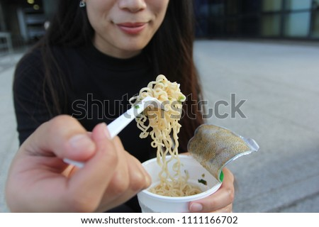 Young woman hand holding plastic fork of instant noodles, Sodium diet high risk kidney failure, Healthy Eating