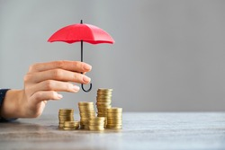 Young woman hand holding small red umbrella over pile of coins on table. Close up of stack of coins with female hands holding umbrella for protection. Financial safety and investment concept.