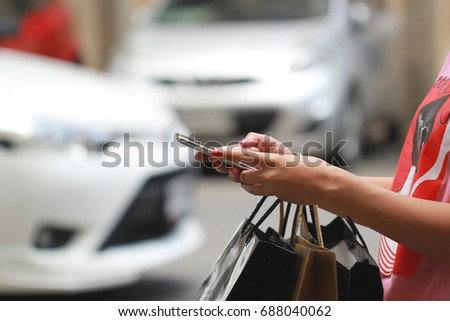 young woman hand holding smartphone and shopping bags with standing at the car parking lot