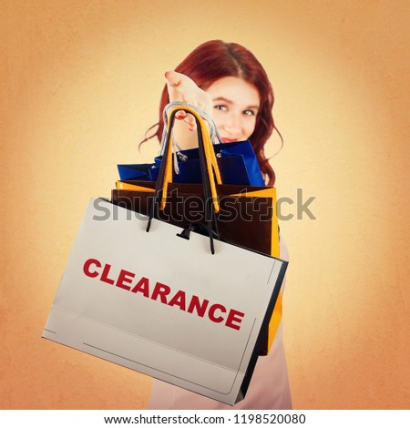 Young woman hand stretched to camera holding shopping bags as stock clearance for sale season isolated over colorful background.