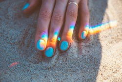 Young woman hand with blue manicure and reflection of rainbow on sand, close-up.