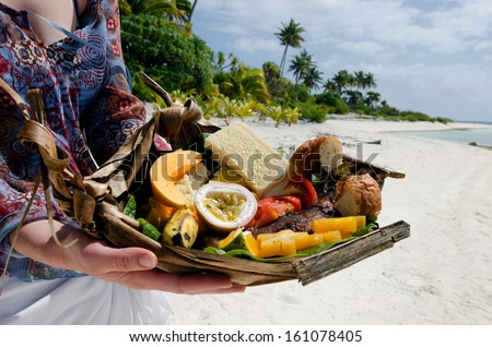 Young woman hands carry tropical food of grilled fish, fruits and vegetables dish served on deserted tropical island in Aitutaki lagoon, Cook Islands.