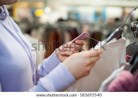 Young woman hands choosing the right clothes for herself and checking prices during sale time