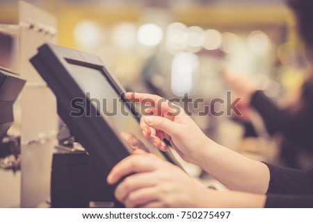 Young woman hands counting / entering discount / sale to a touchscreen cash register, market / shop (color toned image)
