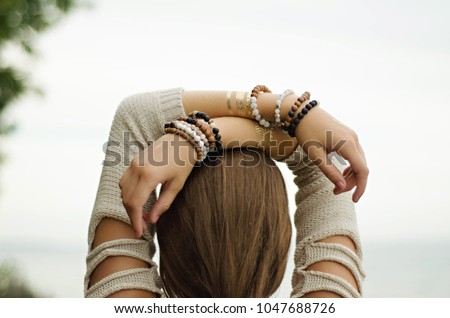 young woman hands crossed over head mala bracelets