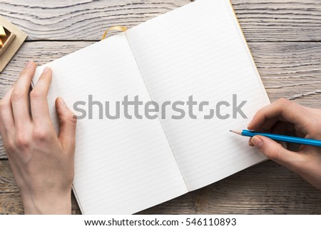 young woman hands hold opened notebook pages with blue pencil in light wooden table with bookmarks