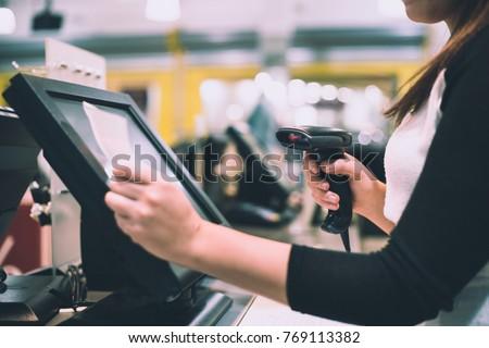 Young woman hands scaning / entering discount / sale on a receipt, touchscreen cash register, market / shop (color toned image)