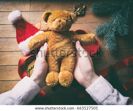 f3860ae1b2960 Young woman hands wrapping christmas teddy bear and gifts on wooden  background