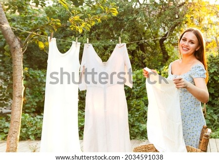Young woman hanging laundry outdoors. Cute girl in dress washing white clothes in metal basin in backyard, hanging laundry on clothesline and leaving it to dry in garden, drying clothes outdoors  Foto stock ©