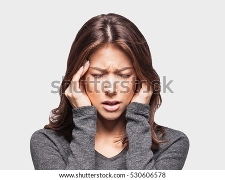 Young woman has headache, isolated on gray background