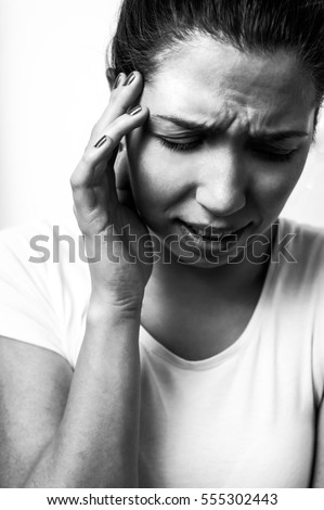 Young woman has painful migraine or strong headache with white background black and white image