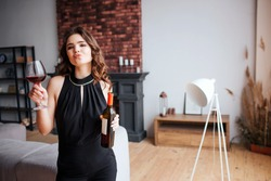 Young woman has problems with alcohol. Beautiful attractive stylish model posing on camera. Hold wine bottle and glass with alcohol. Alone in living room.