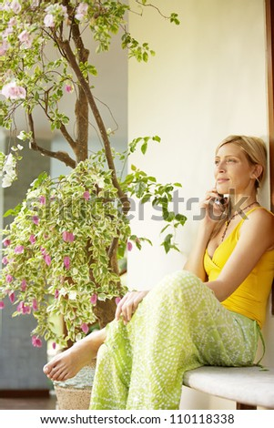 Young woman having a conversation on a cell phone in a home garden.