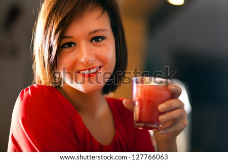 Young woman having a drink in a pub