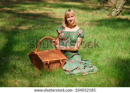 Young woman having a picnic in the forest with fresh fruits and a glass of wine