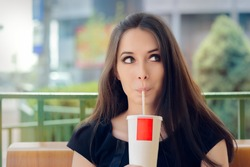 Young Woman Having a Summer Refreshing Drink Outside - Portrait of a funny girl drinking trough a straw