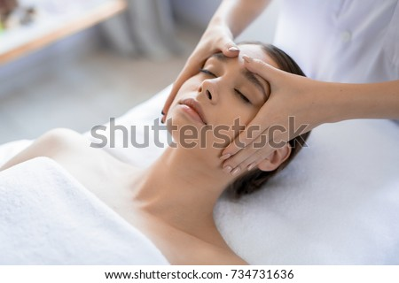 Young woman having anti-stress facial massage in salon at spa resort
