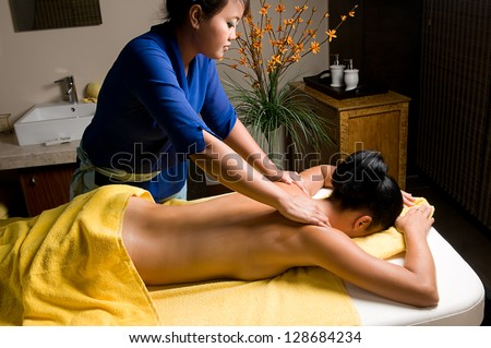 Young woman having Bali style massage at spa salon