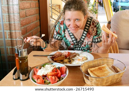 Young woman having breakfast in street cafe
