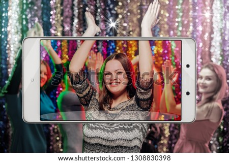 Young woman having dance party in night club, conceptual image with a smartphone