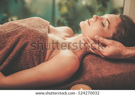 Young woman having face massage in a spa salon.