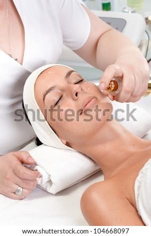 Young woman having facial beauty treatment at beauty salon.