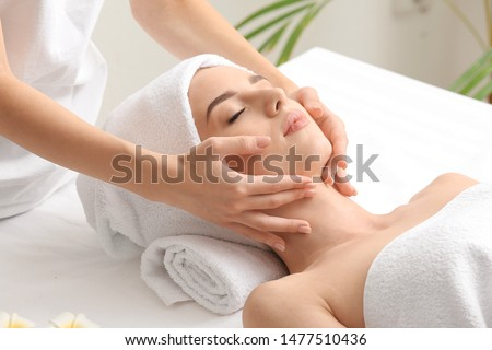 Young woman having facial massage in beauty salon