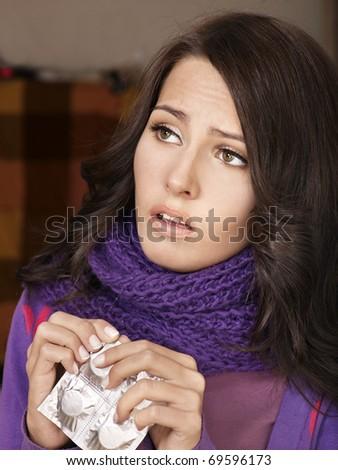 Young woman having flu takes pills.