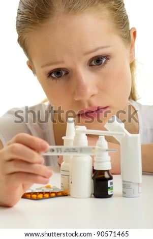 Young woman having flu with thermometer and pills on a white background