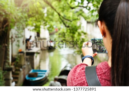young woman having fun in local canal city in China with camera on smartphone making pictures