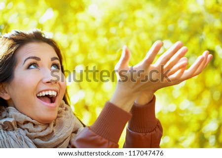 Young woman having fun in the autumn park