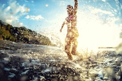 Young woman having fun in the sea with a lot of splashes