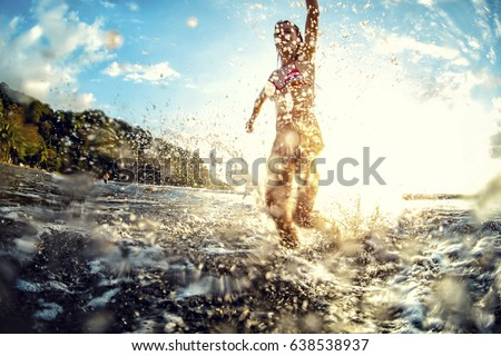 Young woman having fun in the sea with a lot of splashes #638538937