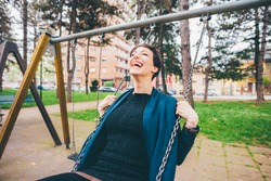 Young woman having fun swinging outdoor - Caucasian young adult feeling free on swing - positive, joyful, happiness concept