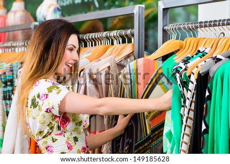 Young woman having fun while fashion shopping in boutique or store