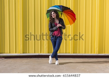 Young woman having fun with a colorful umbrella over yellow background . Lifestyle