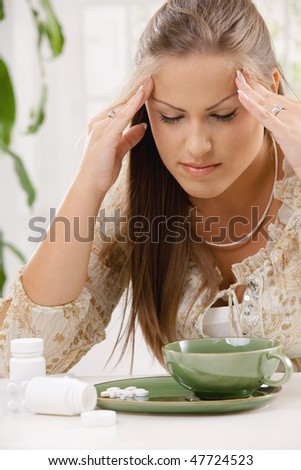 Young woman having headache, holding her head, leaning on table. Taking pills with tea. - stock photo