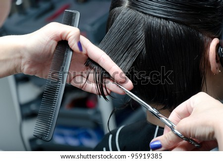 young woman having her hair being cut